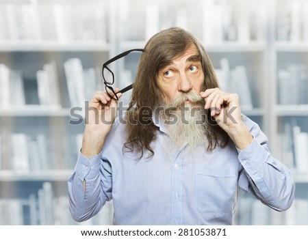 Thoughtful Senior with Glasses Thinking Inspired Looking up. Pensive Old Man with Beard over book library - stock photo