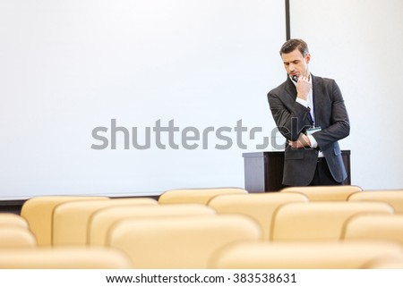 Thoughtful serious businessman standing and thinking in empty conference hall - stock photo