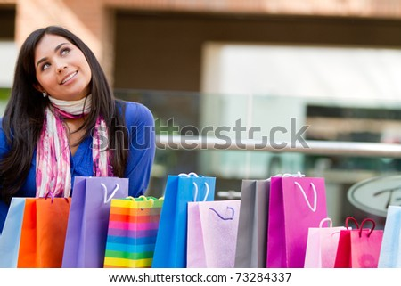 Thoughtful shopping woman with arms up at a mall - stock photo