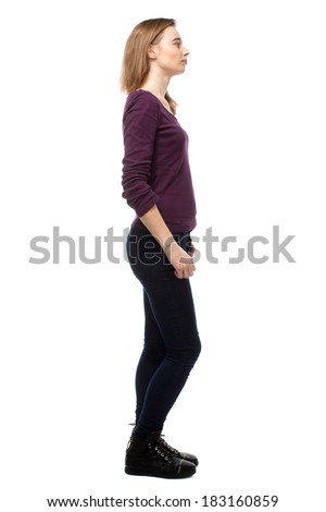 Thoughtful slender young woman in casual clothes standing sideways staring off into the distance with a pensive expression, full length isolated on white - stock photo