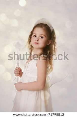 Thoughtful smiling little girl in costume of fairy, studio shot - stock photo