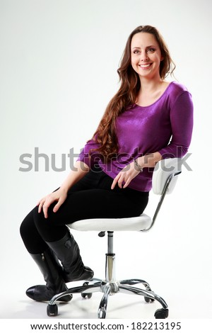 Thoughtful smiling woman sitting on the chair over gray background - stock photo