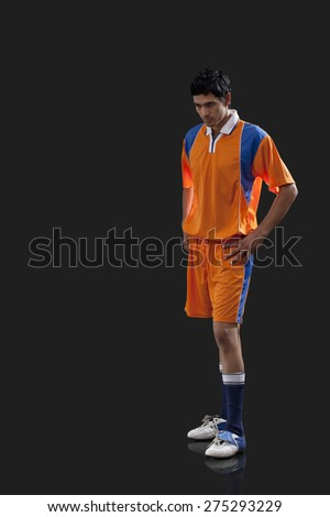 Thoughtful soccer player standing with hands on waist isolated over black background - stock photo