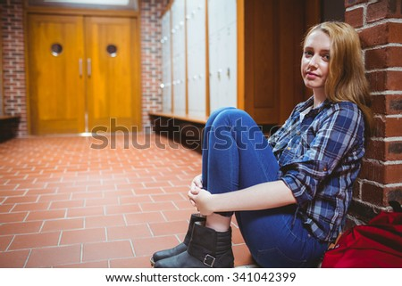 Thoughtful student sitting on the floor against the wall and looking at the camera at the university - stock photo