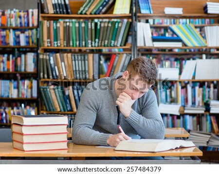 thoughtful student with open book working in a library - stock photo
