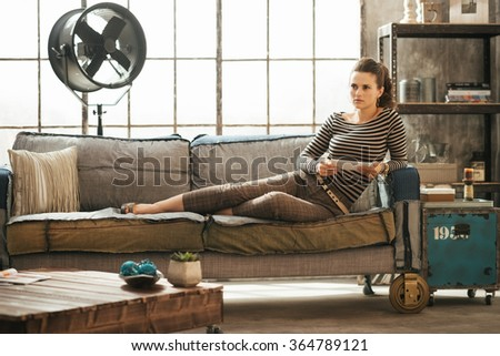 Thoughtful stylish brown-haired woman is sitting on couch and holding tablet PC in loft apartment