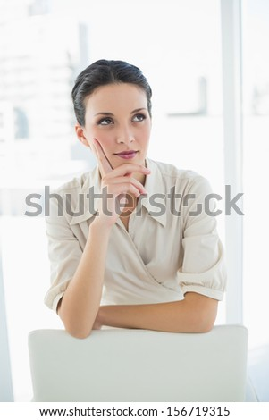 Thoughtful stylish brunette businesswoman posing looking away in bright office