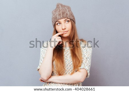 Thoughtful stylish woman looking away over gray background - stock photo
