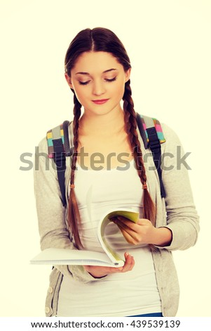 Thoughtful teen woman reading her notebook. - stock photo