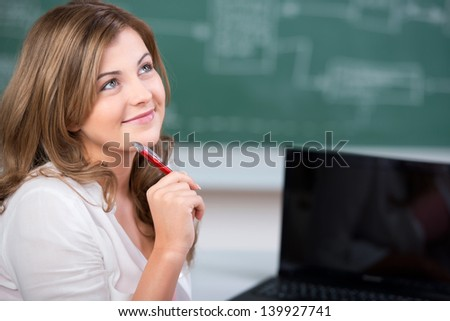 Thoughtful teenage female student holding pen while looking up in classroom