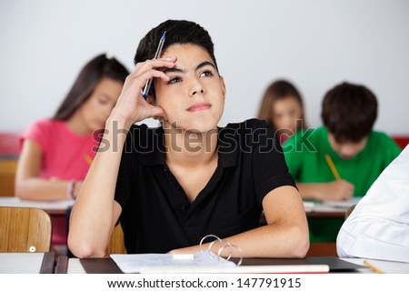 Thoughtful teenage schoolboy looking up while sitting at desk in classroom - stock photo