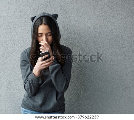 thoughtful teenager girl writes SMS - stock photo