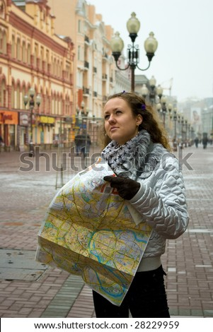 thoughtful tourist girl with map in her hands