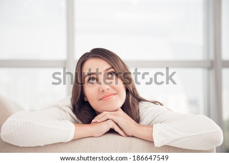 Thoughtful woman at home - stock photo