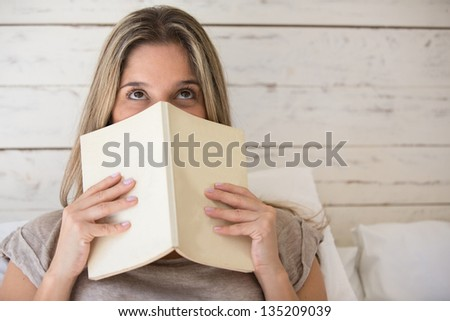 Thoughtful woman at home reading a book