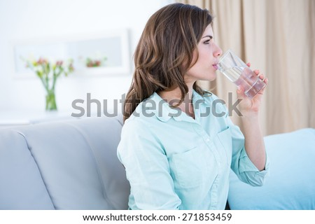 Thoughtful woman drinking a glass of water at home in the living room - stock photo