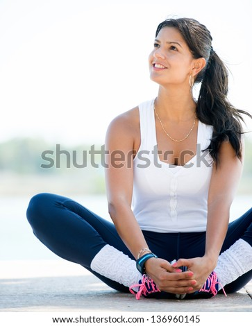 Thoughtful woman exercising outdoors and looking happy - stock photo