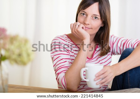 Thoughtful woman holding a cup of coffee with her hand to her chin staring pensively at the camera as she sits at a wooden table - stock photo