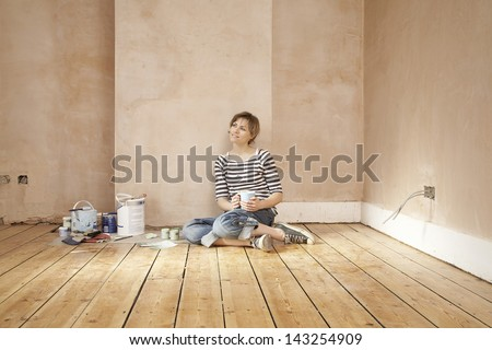 Thoughtful woman holding coffee mug sitting on floorboard - stock photo
