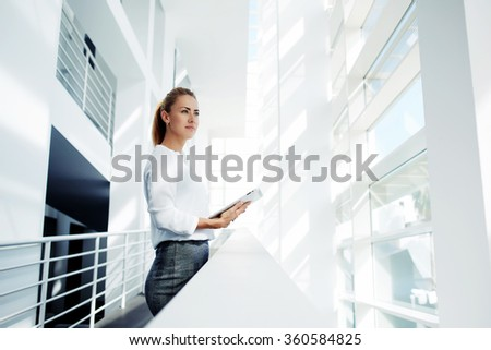 Thoughtful woman holding digital tablet and looks into the window after business meeting with partners, young successful female financier ponders over the future of company during work break in office - stock photo