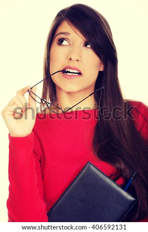 Thoughtful woman holding glasses. - stock photo