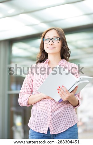 Thoughtful woman looking away while holding book outdoors - stock photo