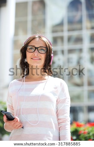 Thoughtful woman looking away while listening music outdoors - stock photo