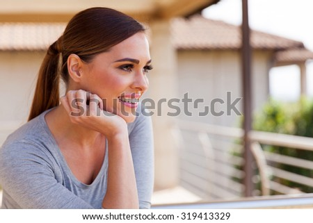 thoughtful woman outdoors on a apartment balcony - stock photo