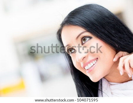 Thoughtful woman portrait  looking up and smiling - stock photo
