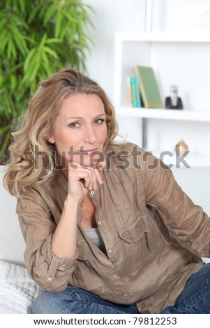 Thoughtful woman sitting in her lounge - stock photo