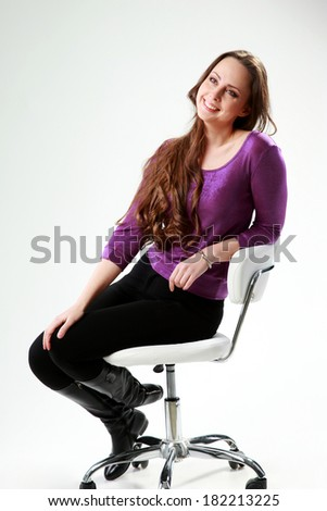Thoughtful woman sitting on the chair over gray background - stock photo