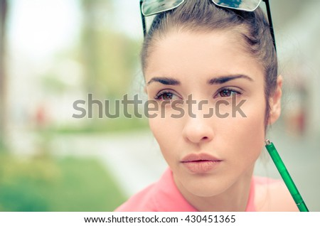 thoughtful woman sitting thinking outdoors with pen near face - stock photo