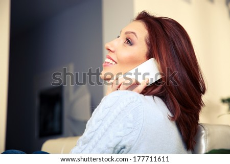 Thoughtful woman talking on the phone and  looking up at home - stock photo