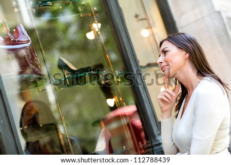 Thoughtful woman window shopping and looking at shoes - stock photo