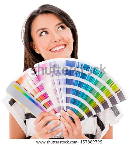 Thoughtful woman with a color guide thinking how to paint - isolated over white - stock photo