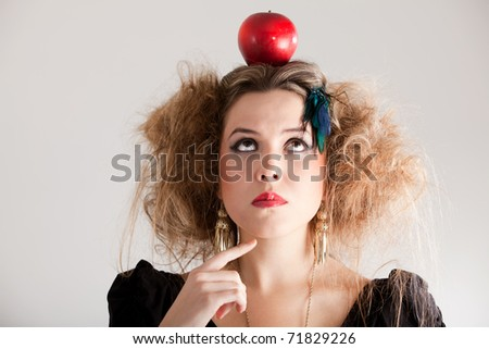 Thoughtful woman with a messy hairdo and an apple on top - stock photo