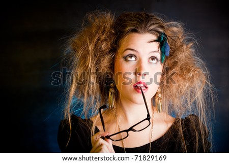 Thoughtful woman with a messy hairdo holding glasses - stock photo