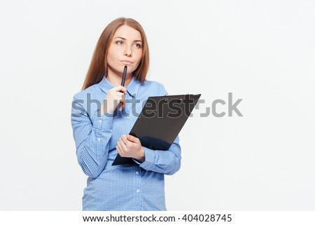 Thoughtful woman with clipboard standing isolated on a white background - stock photo