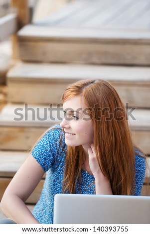 Thoughtful woman with her laptop sitting on wooden steps staring off sideways into the distance - stock photo
