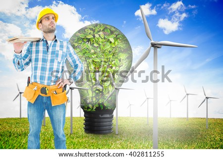 Thoughtful worker carrying wooden planks against wind turbines and bulb full of leaves - stock photo