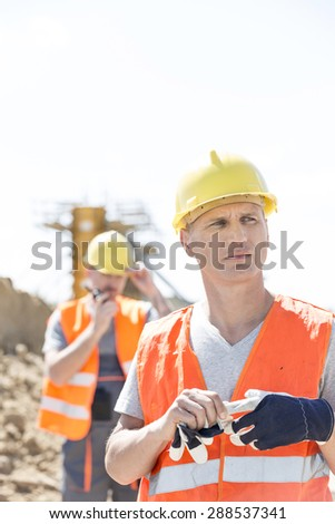 Thoughtful worker standing at construction site with colleague in background - stock photo