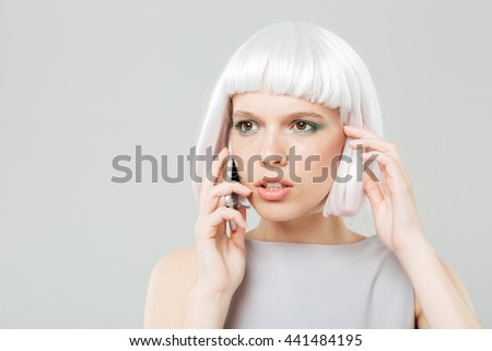 Thoughtful worried young woman in blonde wig talking on mobile phone - stock photo