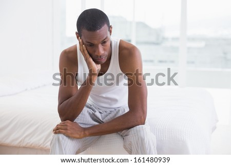 Thoughtful young Afro man sitting on bed at home