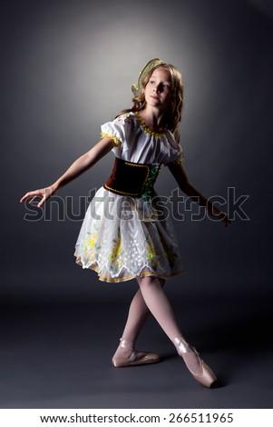 Thoughtful young ballerina dancing in folk dress - stock photo