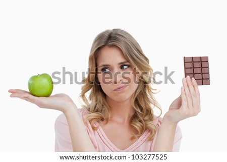 Thoughtful young blonde woman hesitating between a fruit and chocolate - stock photo