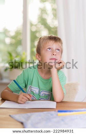 Thoughtful young boy doing his class homework staring up into the air as he searches for an answer to a problem - stock photo