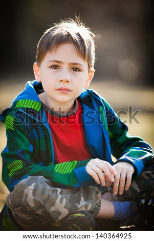 Thoughtful young boy in casual clothes sat in garden or countryside. - stock photo