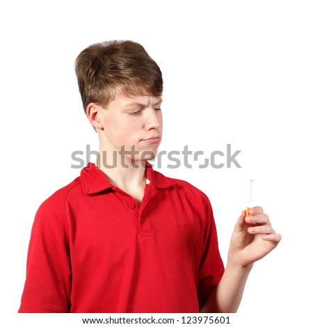 Thoughtful young boy looks at a cigarette - stock photo