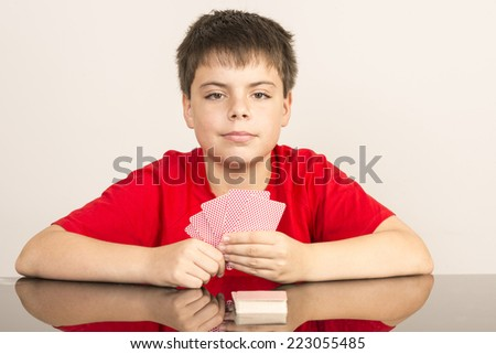 Thoughtful young boy playing cards  looking at camera - stock photo