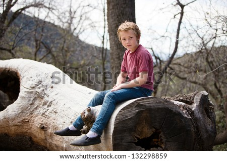 Thoughtful young boy sitting on a log - stock photo
